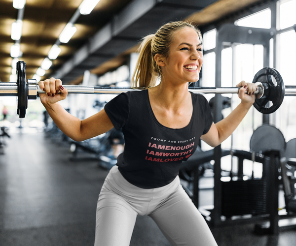 A woman lifting weights at a gym and wearing a scoop neck fitted tee in white with a quote I am enough, I am worthy, I am loved