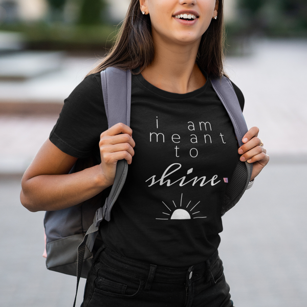 Smiling young woman with a backpack wearing a black t-shirt with a quote I Am Meant to Shine