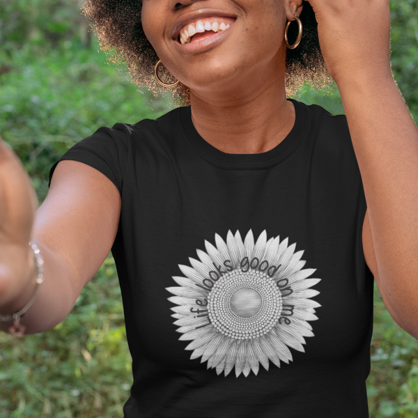 A smiling woman in the woods wearing a black crewneck short sleeve tee with a sunflower design and quote Life looks good on me.