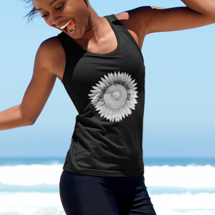 A woman jumping at the beach and wearing a black tank top with a sunflower design and quote Life looks good on me