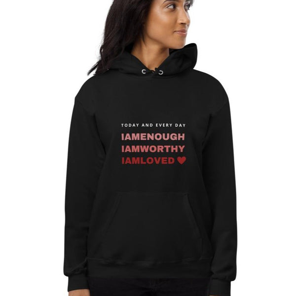 A woman standing at a studio and wearing a hoodie in black with a quote I am enough, I am worthy, I am loved