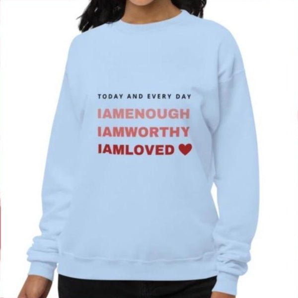 A woman at a studio wearing a crewneck sweatshirt in light blue with a quote I am enough, I am worthy, I am loved