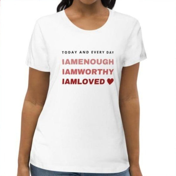 A woman at a studio wearing a scoop neck fitted tee in white with a quote I am enough, I am worthy, I am loved