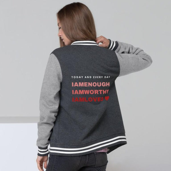 A woman at a studio wearing letterman jacket in graphite heather vintage with a quote on the back I am worthy, I am enough, I am loved