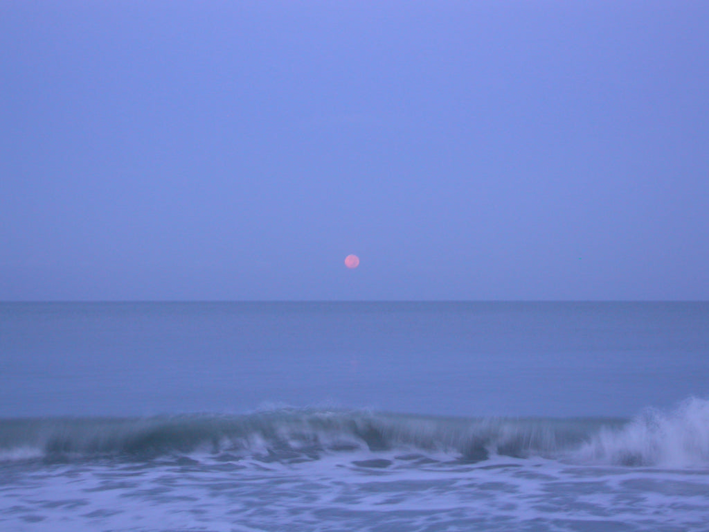 Full moon setting into the Gulf Of Mexico off of Captiva Island, Florida.