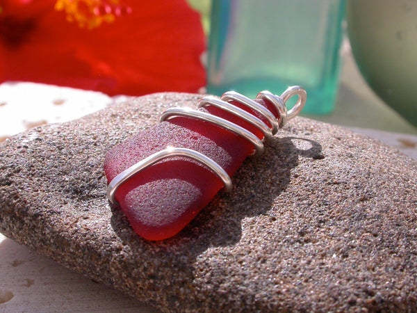 This piece of red sea glass was found on a beach in Rincon, Puerto Rico and is wire wrapped with thick gauge sterling silver wire.