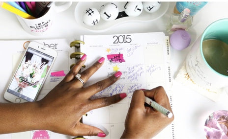 Woman with pink painted fingernails writing in calendar