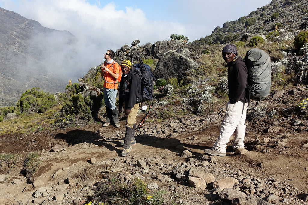 Hikers and guide with clouds in the background on Mount Kilimanjaro Machame Route