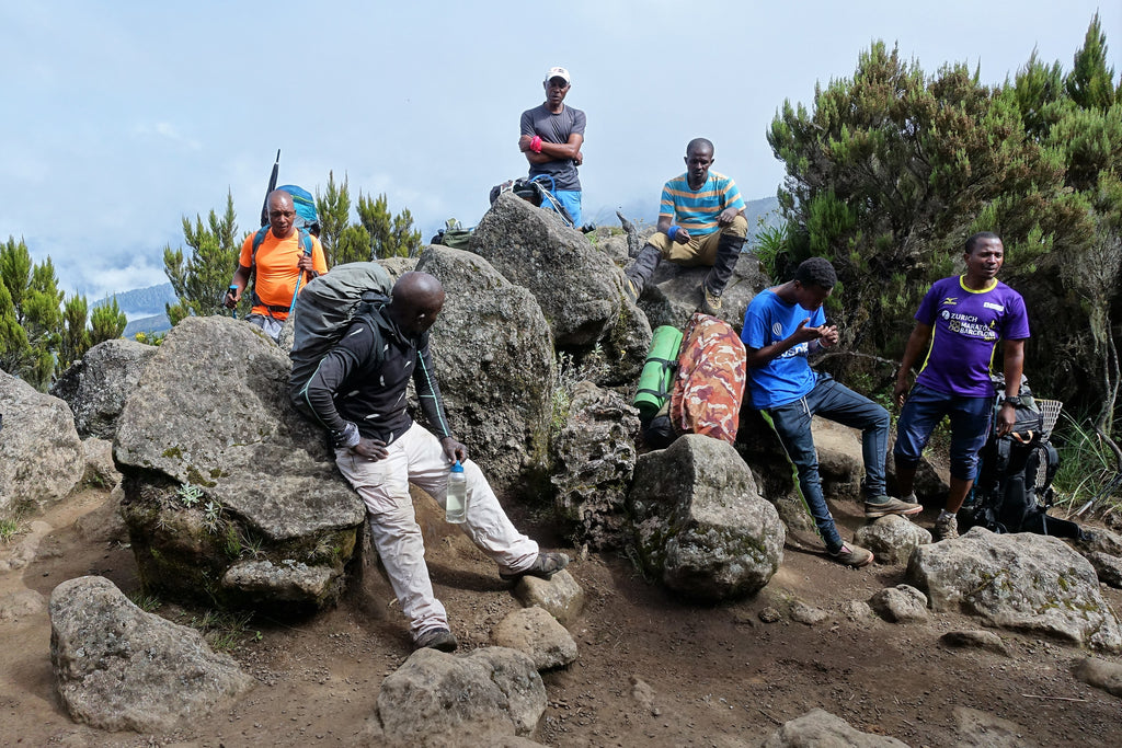 Porters from Zara Company sitting on rocks on Mount Kilimanjaro Machame Route
