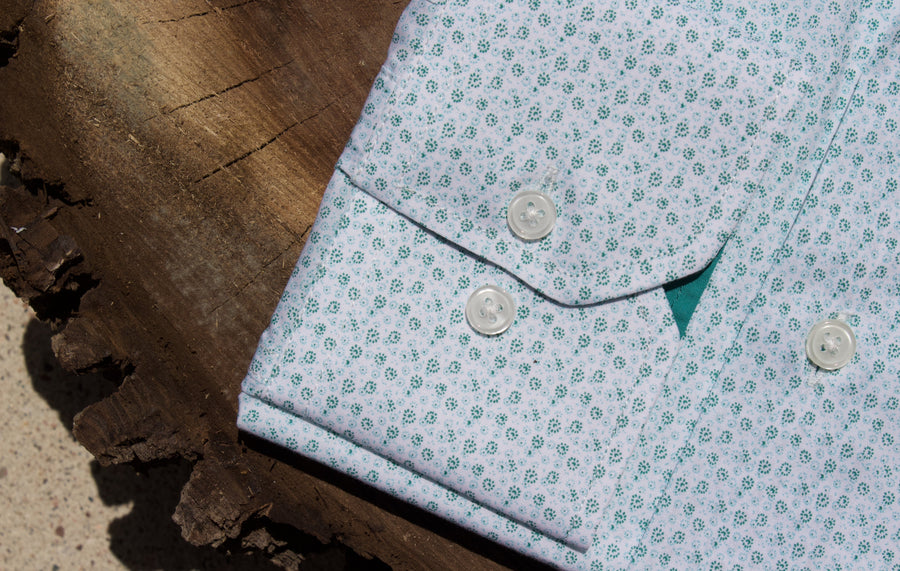 Green floral dress shirt sleeve on slice of walnut tree.