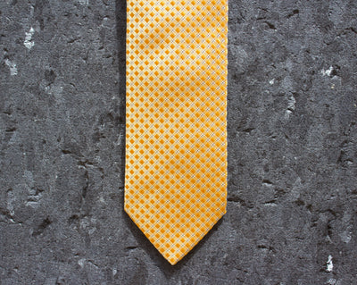Yellow/orange, checked tie against black stone background.