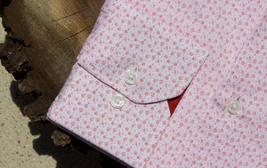 Red floral dress shirt sleeve on slice of walnut tree.