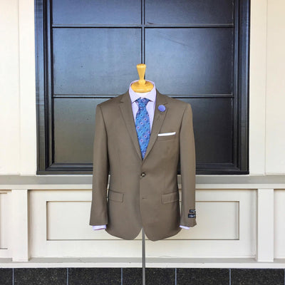 Taupe suit coat on mannequin with lavender shirt, periwinkle tie and lapel pin, and white pocket square against feature wall.