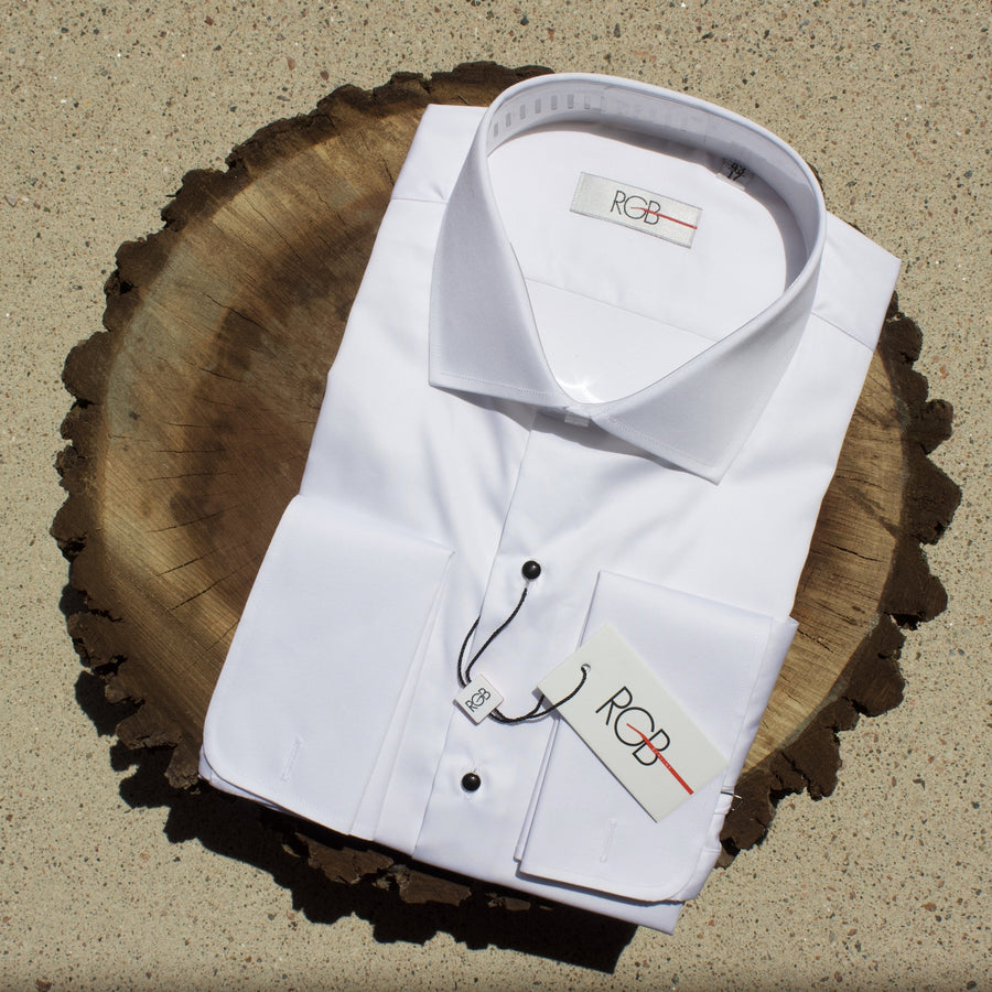 White tuxedo dress shirt with black studs on slice of walnut tree.