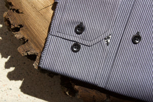 Men's grey and black striped dress shirt sleeve on slice of walnut tree.