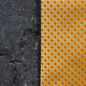 Close up of yellow/orange, checked tie against black stone background.