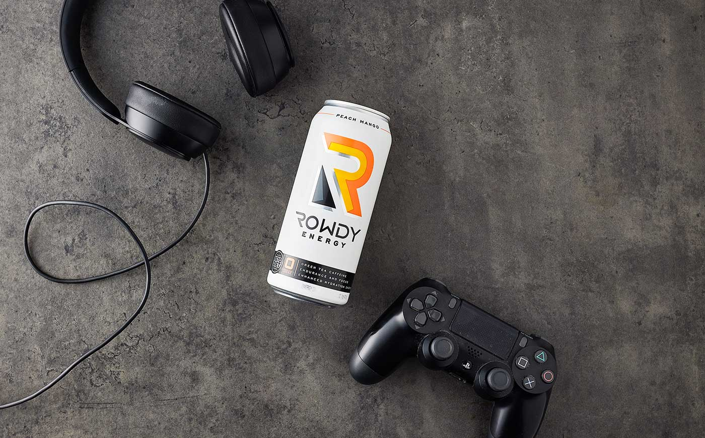 Rowdy Energy Drink on a table next to a game controller and headphones. Rowdy Energy Flavor Peach Mango