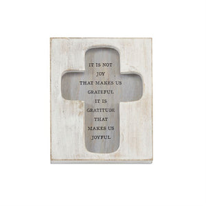"A washed wood block plaque features a recessed cross with a printed ""it is not joy that makes us grateful it is gratitude that makes us joyful""  sentiment."