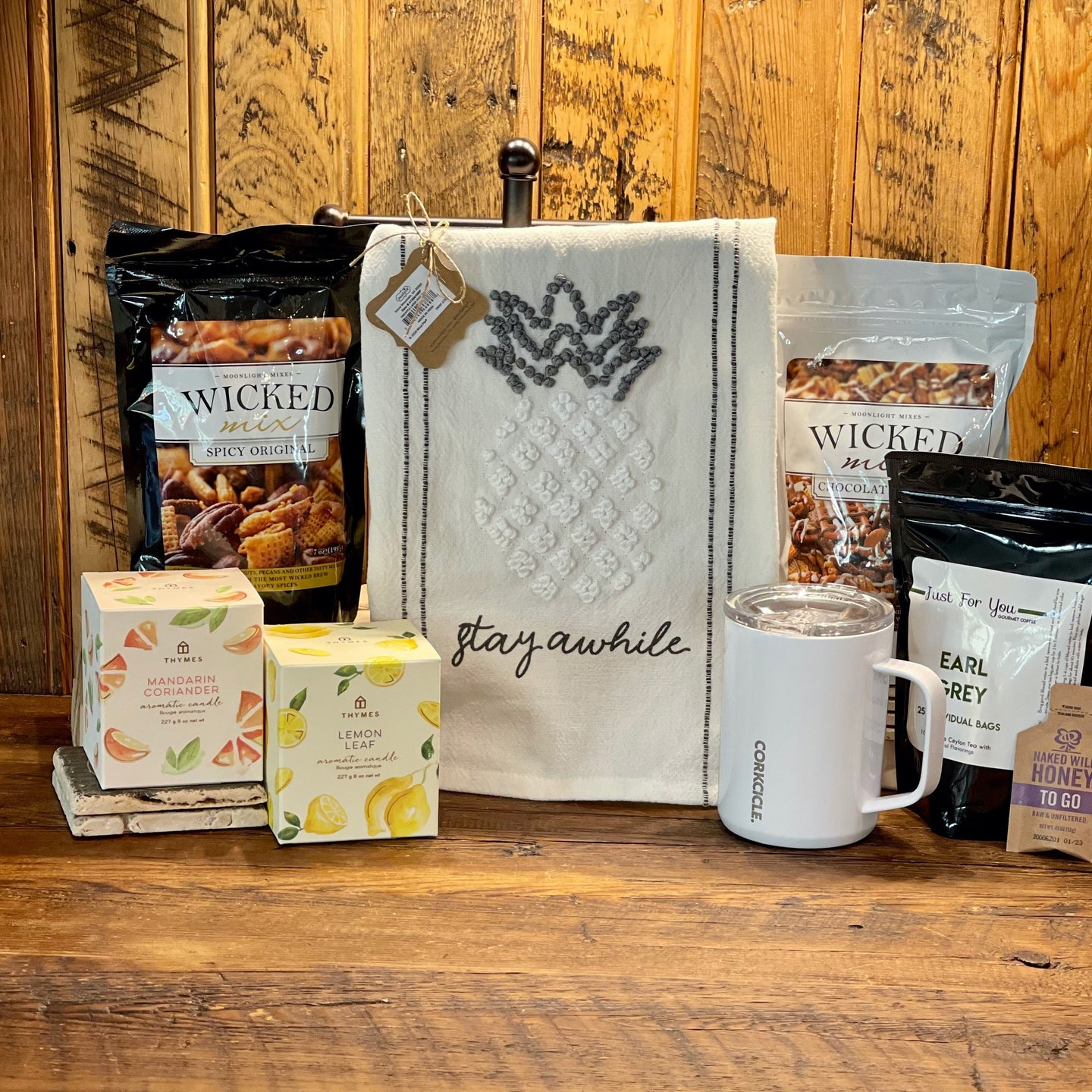 This Box Includes:  Mud Pie Knot Towel (Choose Stay Awhile, Bee Home, Welcome) Wicked Mix (Original or Chocolate) Thymes Candle (Lemon or Mandarine) Corkcicle Coffee Mug  One French Roast Coffee & One Earl Grey Tea w/ Honey