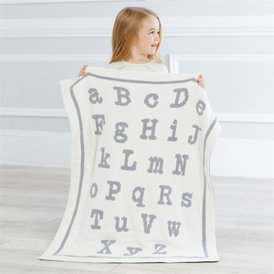 "An incredibly soft double sided chenille knit blanket in cream and grey (features ABC pattern)  Dimensions: 34"" x 28"""