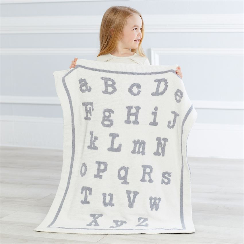 An incredibly soft double sided chenille knit blanket in cream and grey (features ABC pattern)  Dimensions: 34