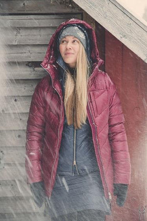 Shot of woman standing in the snow wearing the Skhoop Nuuk Down Parka in Ruby Red