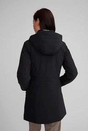 rear view of woman wearing monaco parka in black with both hands in her pockets