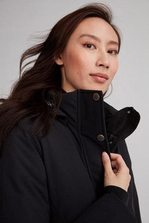 close up of a womans face and shoulders wearing the monaco parka in black