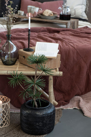 Cosy bed styling with coffe tray and lit candle