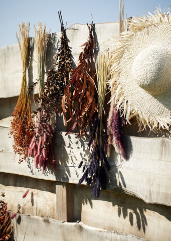 Dried flowers hanging on a wooden fence