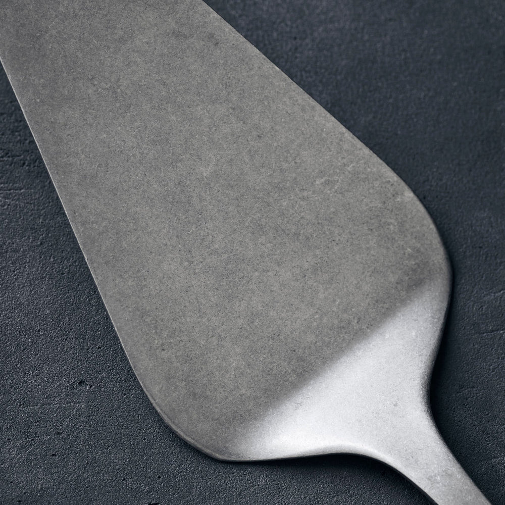 A stainless steel cake server with a hole in the top of the handle for hanging up after use.