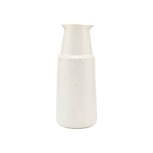 Off-white porcelain bottle with darker speckles in the glaze. Has a ridge near the top and a lip for pouring liquid or sauce.