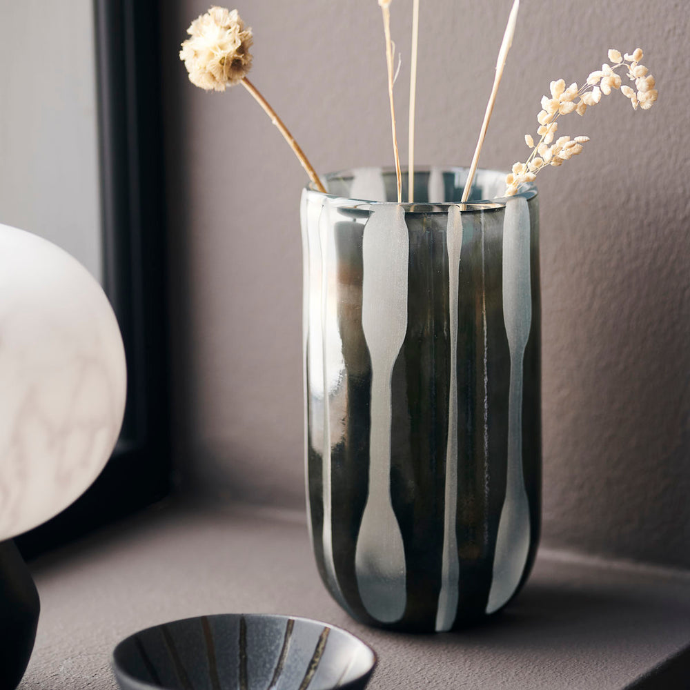 Glass vase with abstract vertical stripes in grey/black glass, in a tall cylindrical shape.