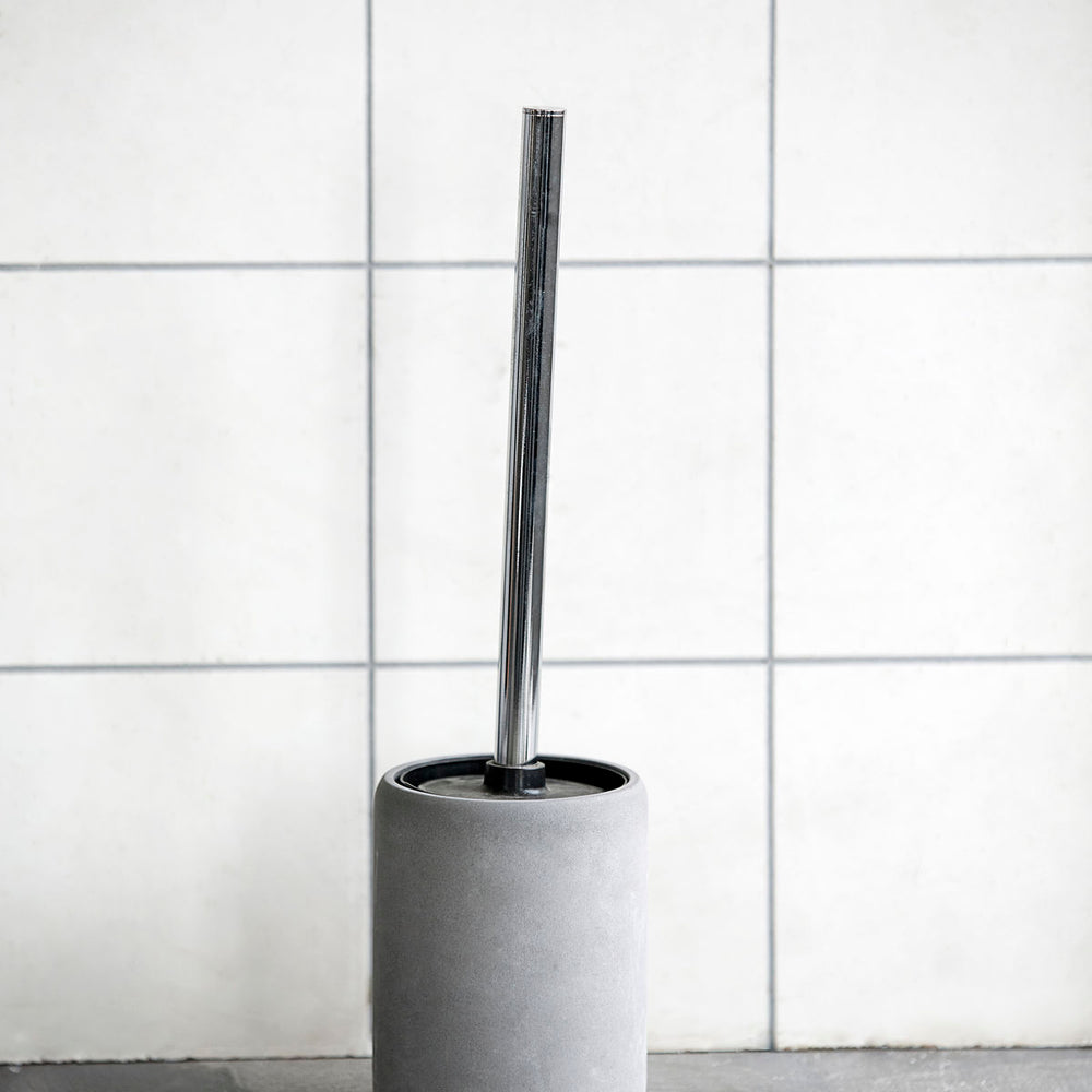Toilet brush with silver shank and black bristles, sitting inside a grey cement pot to hold it.