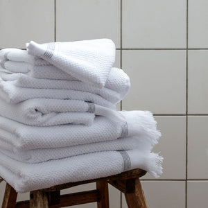 Set of two white towels with 4 grey stripes along the bottom and white fringes along the ends.