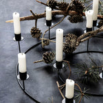 Circular black candle stand made from metal, with eight candle holders at varying heights.