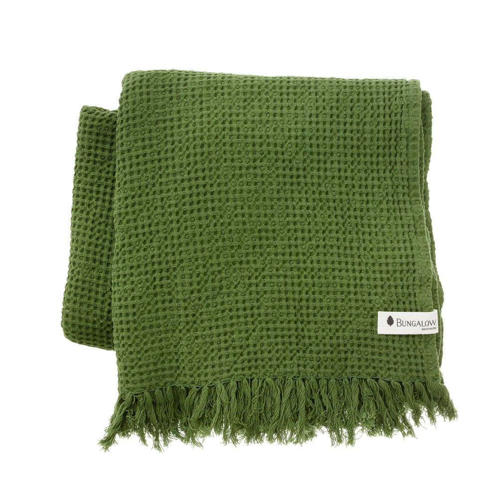 A forest green bath towel with a waffle texture and fringes at the ends. A small white cotton tag on the corner with the 'Bungalow' brand logo printed on.