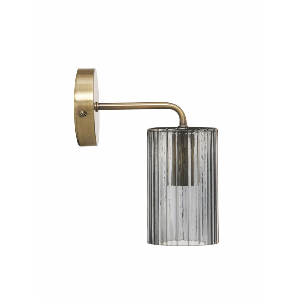 A wall light with circular brass coloured fitting and smoky grey glass shade.