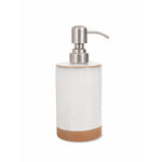 A soap dispenser with a silver metal pump, attached to a part glazed ceramic pot in Off-white with a sandy ceramic base.