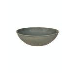 A wide ceramic serving bowl with a blue green glaze and rustic edges.
