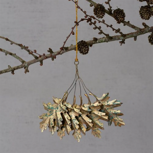 Metal leaves in gold with green, distressed pattern hanging from wire attached to a loop for hanging.