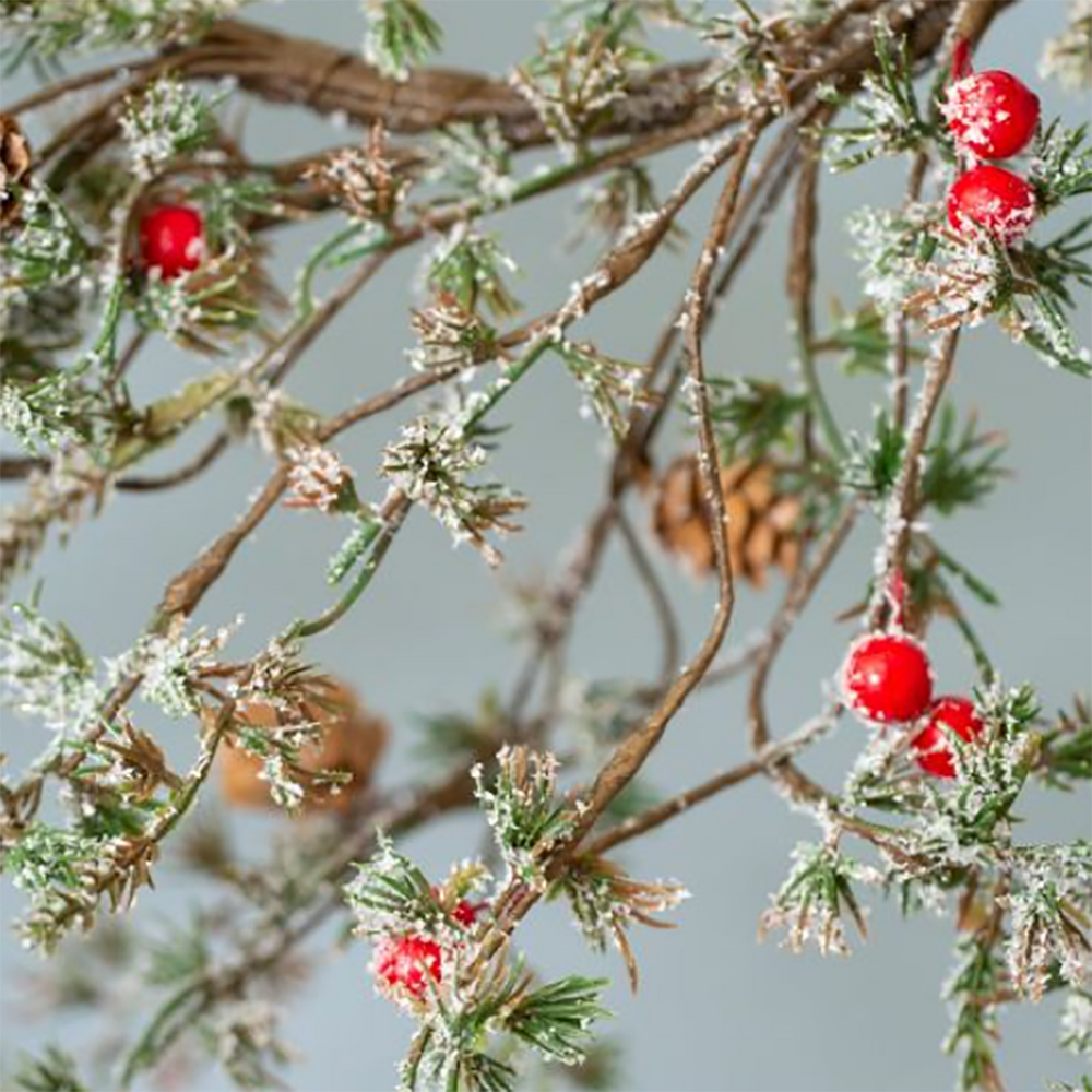 A ring of artificial larch style branches with red berries and white frosting.
