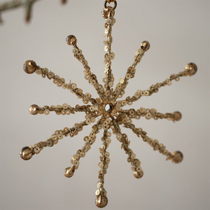 A gold snowflake shape made of metal with gold sequins and beads decorating each of the 12 spikes. Hanging from a loop of gold string.
