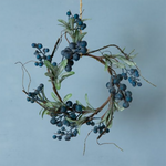 A ring of artificial branches with blue berries decorating and green leaves.