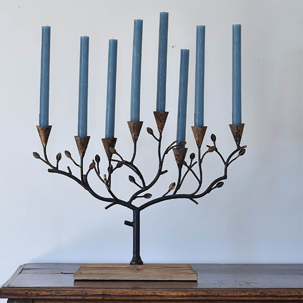 A tree shaped candle holder with 8 branches at different levels that have a candle holder at each end. Made of a rustic, brown metal attached to a podium of smooth wood.