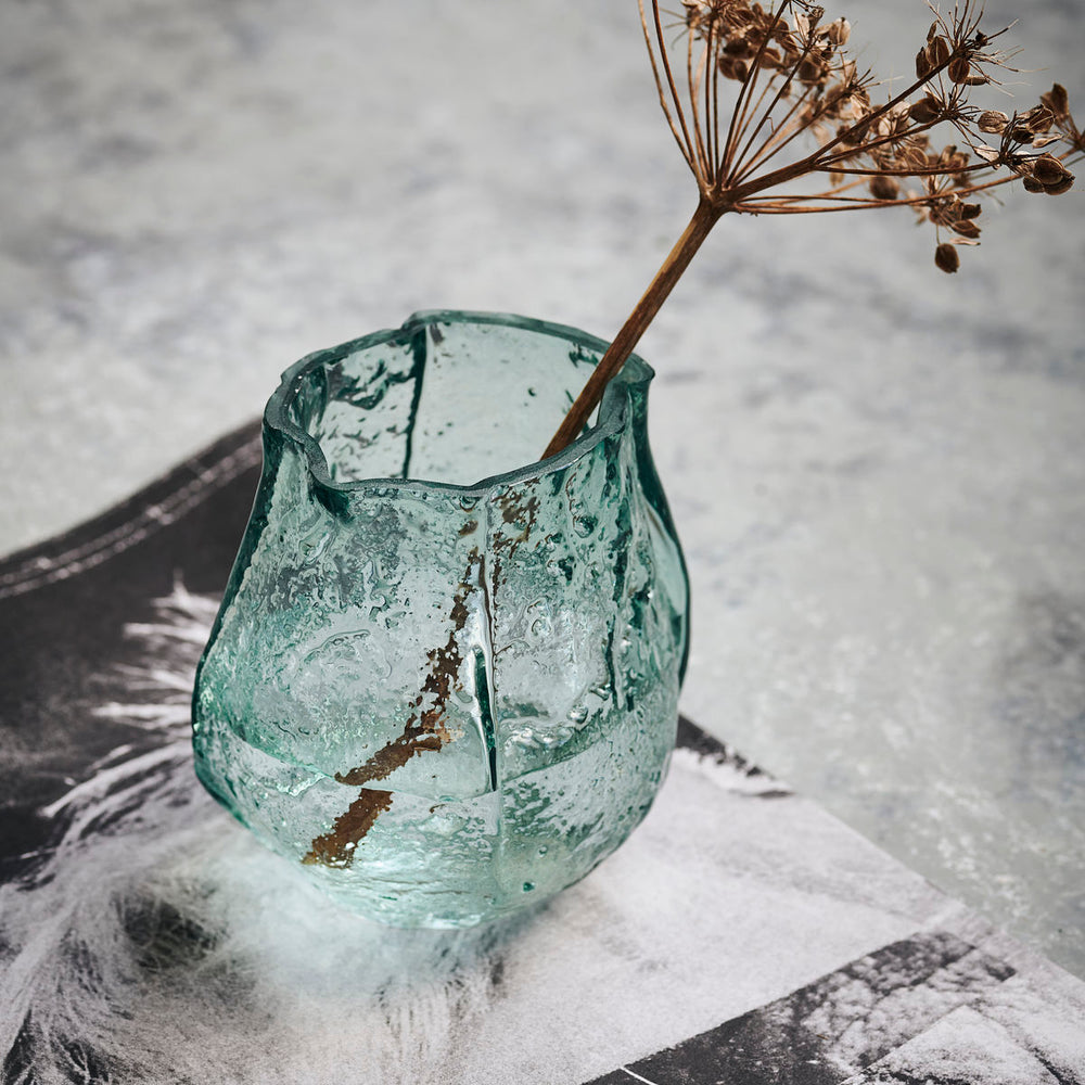 A small, clear light blue coloured glass vase in an asymmetrical shape. The glass has bumps and textures all over to make a ripple effect.