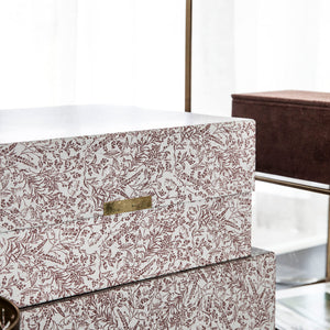 Two storage boxes, one large and one smaller, in a grey colour with burgundy red flower patterns printed on. There is a rectangular brass magnetic clasp on the front of each box.