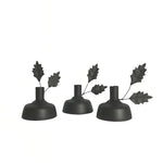Three small metal candle holders in black, with two mistletoe leaves on wire stalks coming out of the left hand side and a larger base to keep the candle balanced.