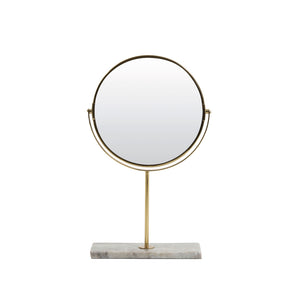 A round antique brass coloured mirror held on either side by brass semi circle shape on a central brass pole, with a rectangular grey marble base at the foot.