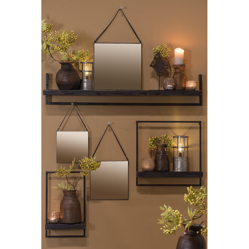 A square mirror with black metal border and back, hung from a length of black cord.